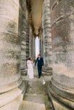 Jeunes couples de mariage posant entre les rangées des colonnes antiques de bâtiment Photos stock