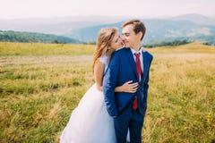 Jeunes couples de mariage posant sur le champ ensoleillé avec Forest Hills éloigné comme fond Jeune mariée espiègle tenant son ma Photographie stock libre de droits
