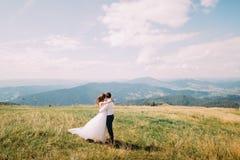 Jeunes couples de mariage posant sur le champ ensoleillé venteux avec Forest Hills éloigné comme fond Photos libres de droits