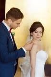 Jeunes couples de mariage souriant contre un mur d'or image stock