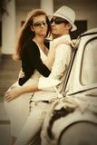 Jeunes couples de mode dans l'amour à côté de la voiture de vintage Images libres de droits
