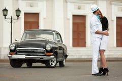 Jeunes couples de mode dans l'amour à la rétro voiture Photos stock