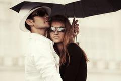 Jeunes couples de mode dans l'amour avec le parapluie dans la rue de ville Photos libres de droits