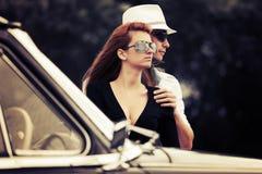 Jeunes couples de mode dans l'amour en la rétro voiture Photographie stock libre de droits