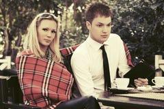 Jeunes couples de mode dinant à un café de trottoir Images stock