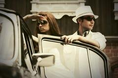 Jeunes couples de mode en conflit à côté de voiture de vintage Photographie stock libre de droits