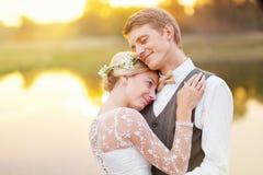 Jeunes couples de nouveaux mariés par le lac Image libre de droits