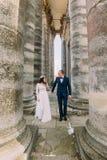 Jeunes couples de nouveaux mariés posant entre les rangées des colonnes antiques de bâtiment Image stock