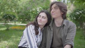 Jeunes couples de portrait dans des vêtements sport se reposant au banc parlant et tenant des mains Temps heureux de d?pense de f banque de vidéos