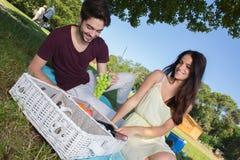Jeunes couples de portrait pendant le pique-nique romantique dans la campagne Photo libre de droits