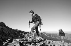 Jeunes couples de randonneur montant rocheux le dessus de montagne Image libre de droits