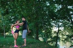 Jeunes couples de santé faisant étirant la détente et l'échauffement d'exercice après avoir pulsé et couru en parc Images libres de droits