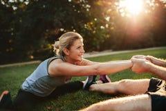 Jeunes couples de santé s'exerçant en parc Image stock