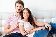 Jeunes couples de Smilling sur le sofa au-dessus du fond blanc Images stock