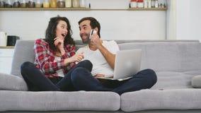 Jeunes couples de sourire appréciant le café de matin avec un ordinateur tout en se reposant sur le divan à la maison ensemble, l clips vidéos