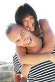 Jeunes couples de sourire ayant l'amusement à la plage Photos libres de droits