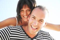 Jeunes couples de sourire ayant l'amusement à la plage Image stock
