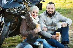 Jeunes couples de sourire ayant le pique-nique avec du café Image libre de droits