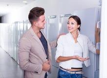 Jeunes couples de sourire choisissant le nouveau réfrigérateur dans l'hypermarché Images stock