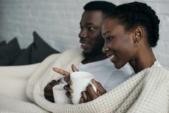 jeunes couples de sourire d'afro-américain tenant des tasses et regardant loin photos libres de droits