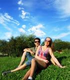 Jeunes couples de sourire dans des lunettes de soleil se reposant en parc dans le jour ensoleillé amitié, loisirs, concept d'été Photos stock