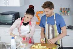 Jeunes couples de sourire faisant cuire le tarte à la cuisine à la maison Photo libre de droits