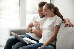 Jeunes couples de sourire faisant l'appel visuel sur la main de ondulation d'ordinateur portable Photos stock