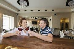 Jeunes couples de sourire grillant des verres de vin au compteur de restaurant Photos libres de droits