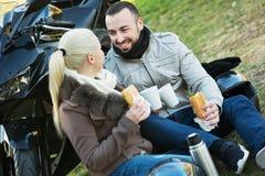 Jeunes couples de sourire heureux ayant le pique-nique avec du café Photos stock