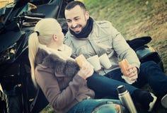 Jeunes couples de sourire heureux ayant le pique-nique avec du café Photographie stock libre de droits