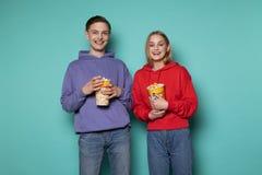 Jeunes couples de sourire heureux dans des v?tements sport se tenant contre le mur bleu avec le ma?s ?clat? dans des mains photos stock