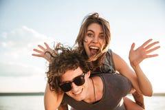 Jeunes couples de sourire heureux dans le ferroutage d'amour à la plage Photo libre de droits