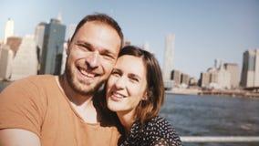 Jeunes couples de sourire heureux posant pour une photo de selfie, embrassant à la vue célèbre d'horizon de New York des gratte-c banque de vidéos