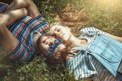 Jeunes couples de sourire heureux se trouvant sur l'herbe dans le domaine Photo stock