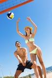 Jeunes couples de sourire jouant le volleyball Photographie stock