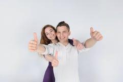 Jeunes couples de sourire montrant des pouces  Image stock