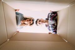 Jeunes couples de sourire ouvrant une boîte de carton et regardant à l'intérieur, la relocalisation et déballant le concept images libres de droits