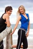 Jeunes couples de sourire par Fence à la plage Photographie stock
