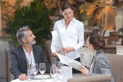 Jeunes couples de sourire de portion de serveuse dans le restaurant photographie stock