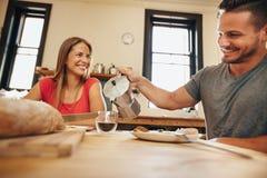 Jeunes couples de sourire prenant le petit déjeuner ensemble dans la cuisine Photos stock