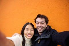 Jeunes couples de sourire prenant un selfie avec le téléphone portable Photo stock