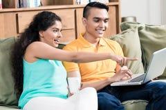 Jeunes couples de sourire regardant l'ordinateur portable photos libres de droits