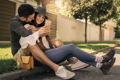 Jeunes couples de sourire se reposant ensemble dehors Image stock