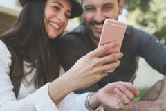 Jeunes couples de sourire se reposant ensemble dehors Photo stock