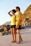 Jeunes couples de sourire se tenant à la plage Photographie stock libre de droits