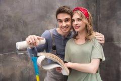 Jeunes couples de sourire se tenant ainsi que des échantillons de rouleau et de couleur de peinture Photos libres de droits