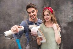 Jeunes couples de sourire se tenant ainsi que des échantillons de rouleau et de couleur de peinture Photographie stock