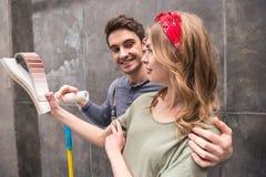 Jeunes couples de sourire se tenant ainsi que des échantillons de rouleau et de couleur de peinture Image libre de droits
