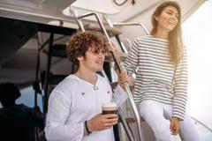 Jeunes couples de sourire tenant des verres avec la boisson tout en voyageant sur le yacht Image libre de droits