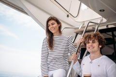 Jeunes couples de sourire tenant des verres avec la boisson tout en voyageant sur le yacht Images stock